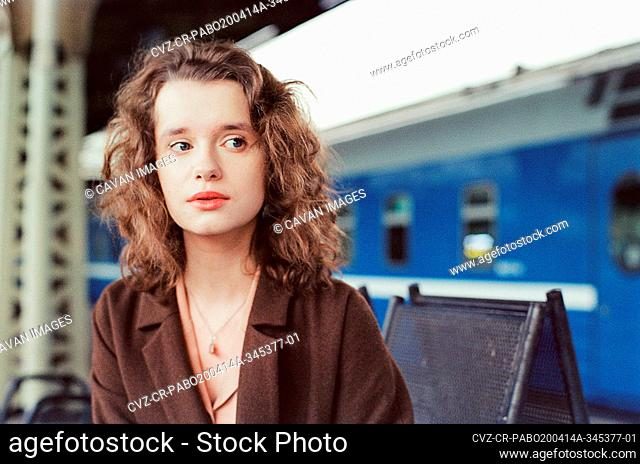 A woman stands near a train at a train station