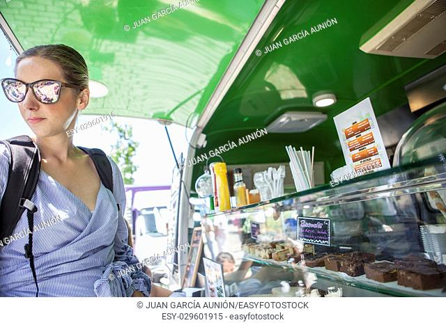 Merida, Spain - May 14, 2017: Young atractive woman ordering meal at green food truck, in the historical city of Merida, Extremadura, Spain