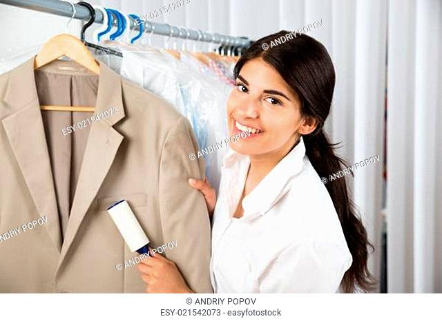 Female Cleaner In Laundry Shop Removing Lint From Clothes With Adhesive Roller