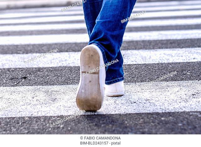 Legs of African American woman walking in crosswalk