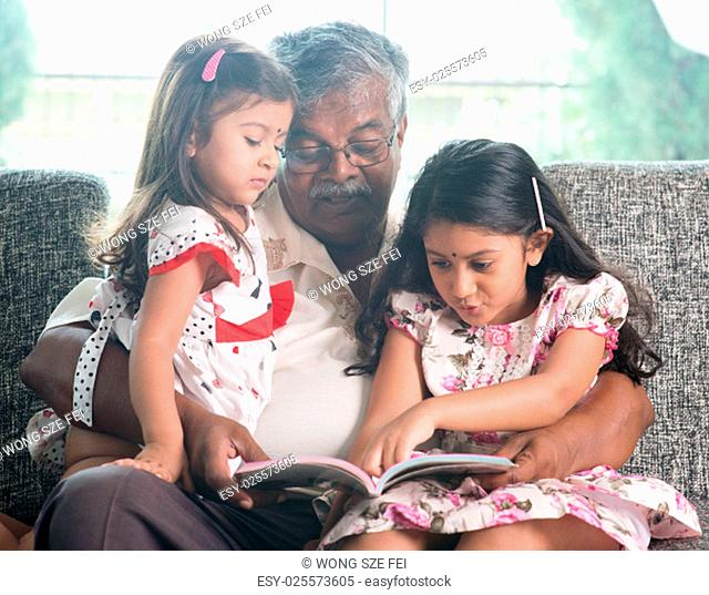 Asian grandfather and granddaughters reading story book. Happy Indian family at home. Grandparent and grandchildren indoor lifestyle