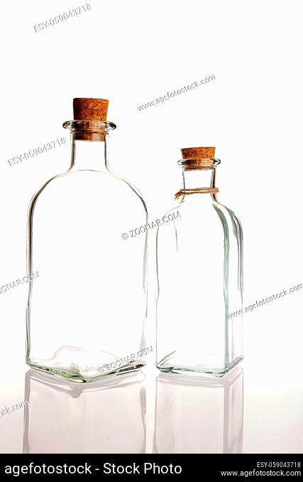 two glass bottles with cork on a white background with reflection