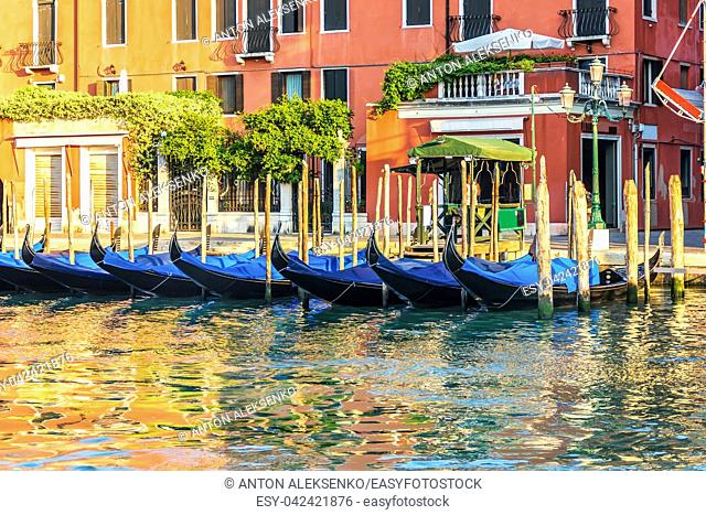 Traditional gondolas by the pier in the channel of Venice