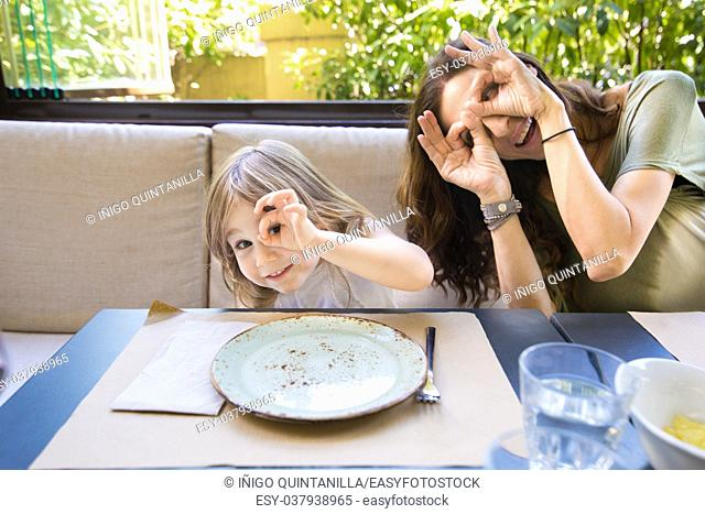 Funny family expression and gesture. Four years age blonde happy girl woman mother teasing and grimacing with fingers in eyes sitting in restaurant