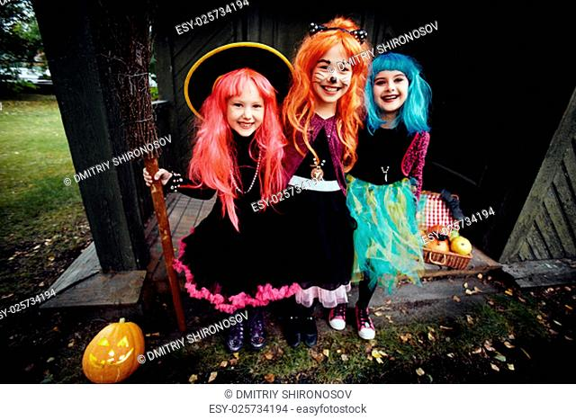 Halloween witches looking at camera by haunted house