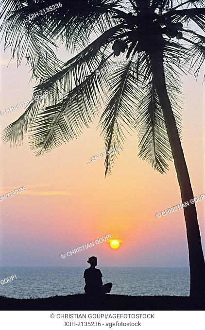 young woman meditating at sunset on top of cliff at Varkala, Thiruvananthapuram district, State of Kerala, India, South Asia