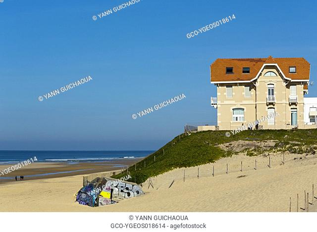 On the seacoast, a traditional house dated XIXth century. On the left a ruin of german bunker from the World War II. Th people is walking on the sand
