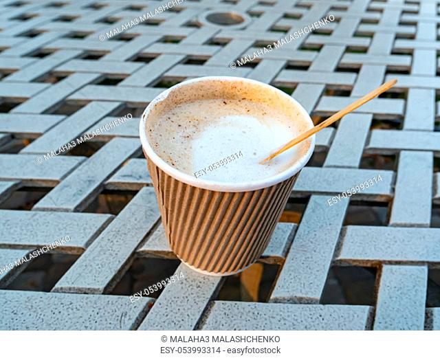 Paper cup with coffee drink on the table. Beverages. Backgrounds. Place for text