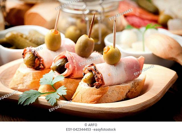 Spanish cuisine. Tapas with sliced bacon, olives and cucumber on a wooden table. on a wooden table