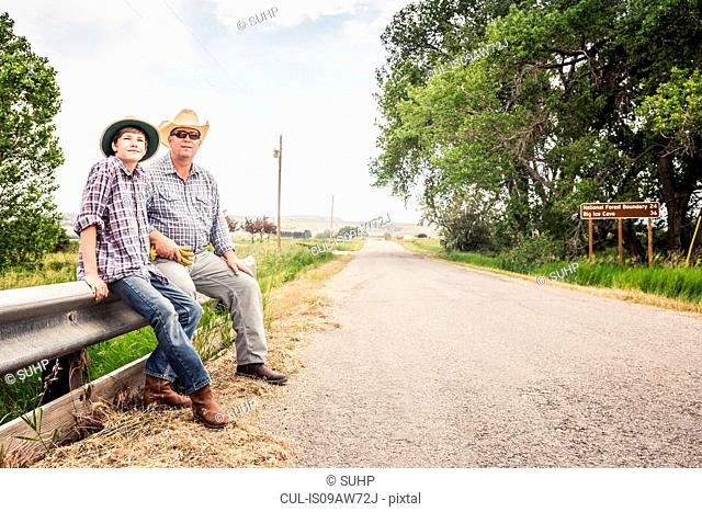 Farmer and teenage grandson sitting on road barrier