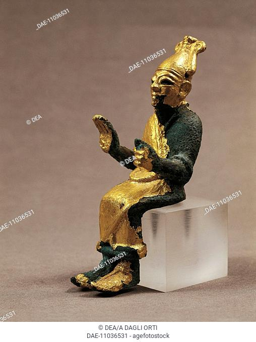 Gold-leafed bronze statuette depicting a seated deity giving a blessing. Artefact from Ugarit (today Ras Shamra), Syria. Assyrian civilisation, ca 1300 BC