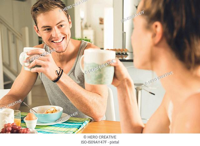 Young couple drinking breakfast coffee at kitchen table