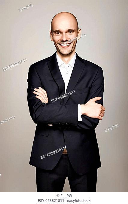 Studio shot of smiling bald man on gray background