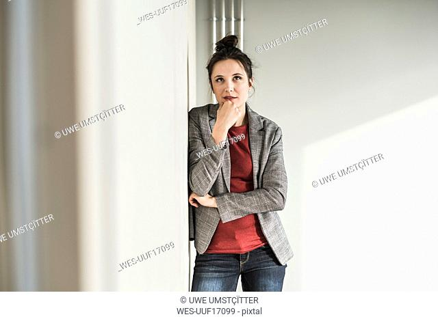 Portrait of businesswoman leaning against a wall in office thinking