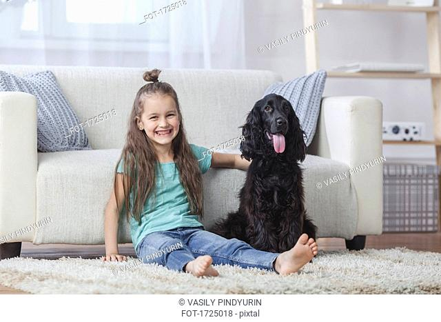 Portrait of cute girl sitting by Cocker Spaniel on rug at home