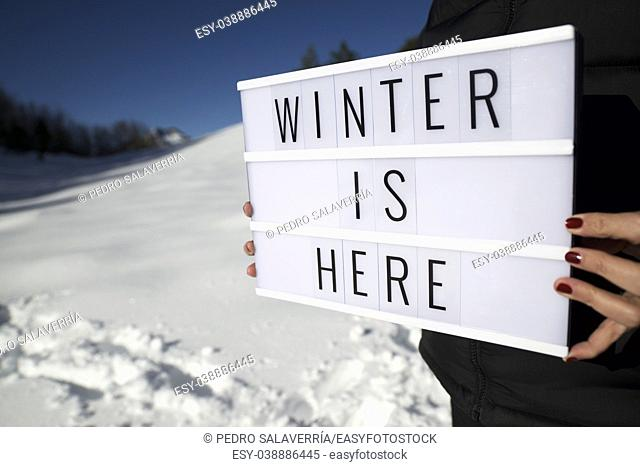 "Slogan """"winter is here"""" held by a woman in a snowy landscape"