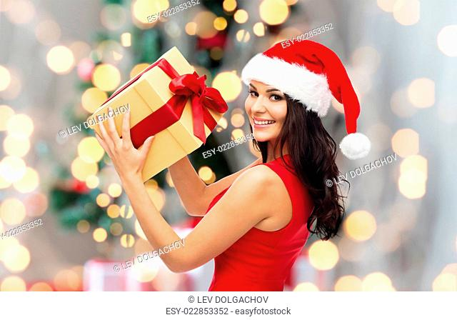 people, holidays, christmas and celebration concept - beautiful sexy woman in red dress and santa hat with gift box over lights background