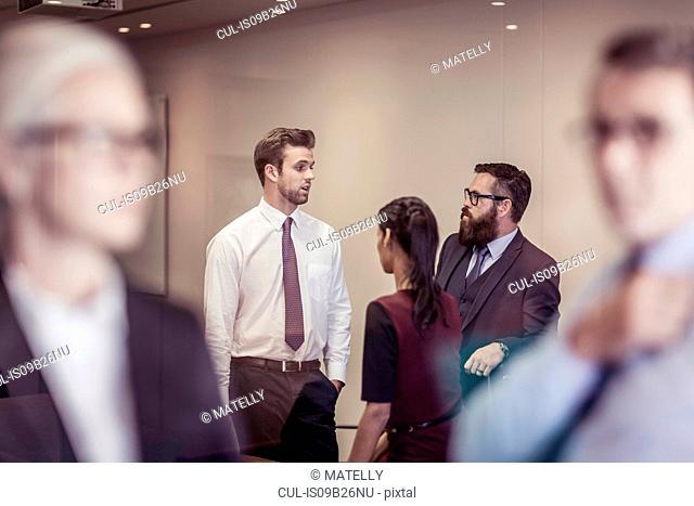 Businesswomen and men chatting in boardroom