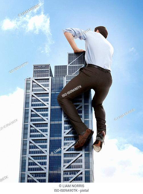 Oversized businessman climbing skyscraper, low angle view