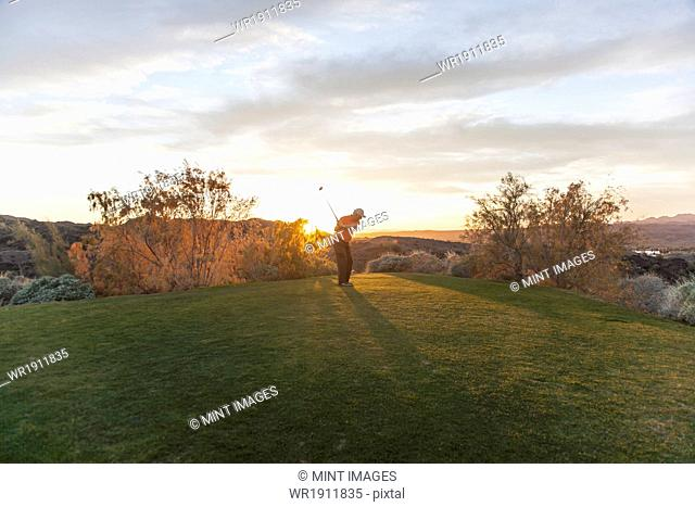 A man taking a shot off a golf tee on a golf course into the sunset