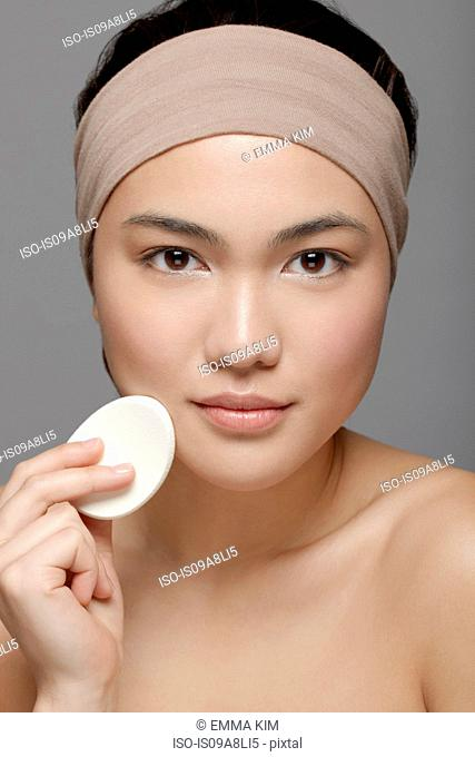 Young woman using make up sponge