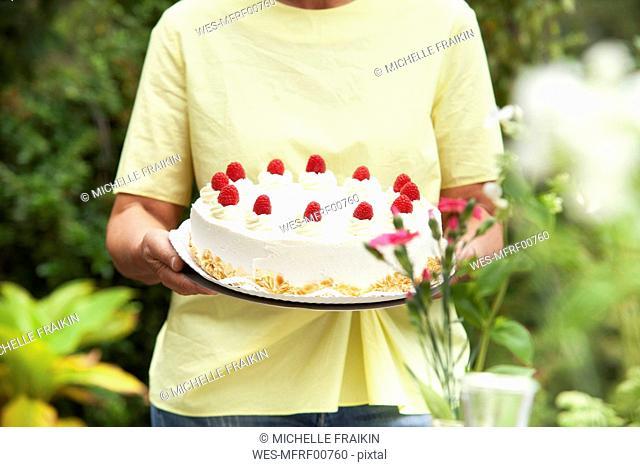 Mature woman serving cream cake in garden