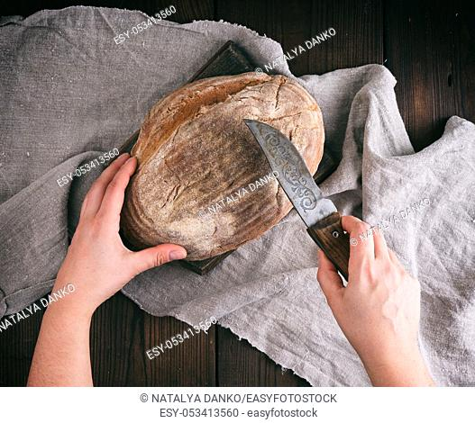 female hands holding a knife over a baked loaf of bread, wooden background, top view