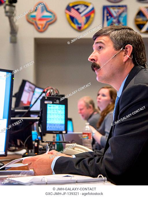 Flight director Mike Sarafin studies a simulated scene on a large screen (out of frame), as a flight control team of about two dozen JSC-based personnel...