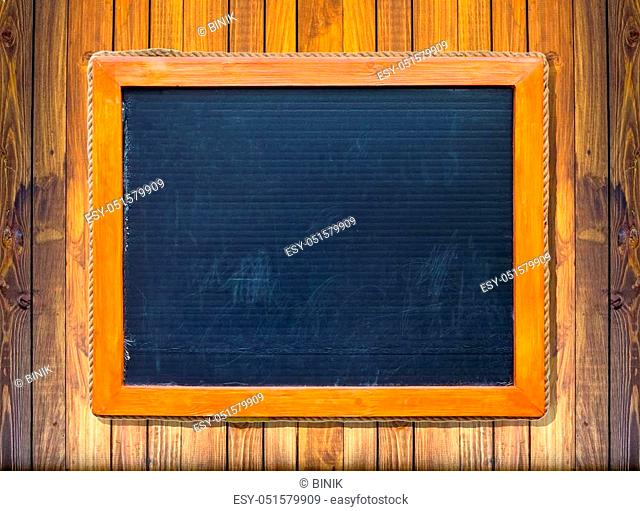 Front view of a blank blackboard over weathered wooden surface