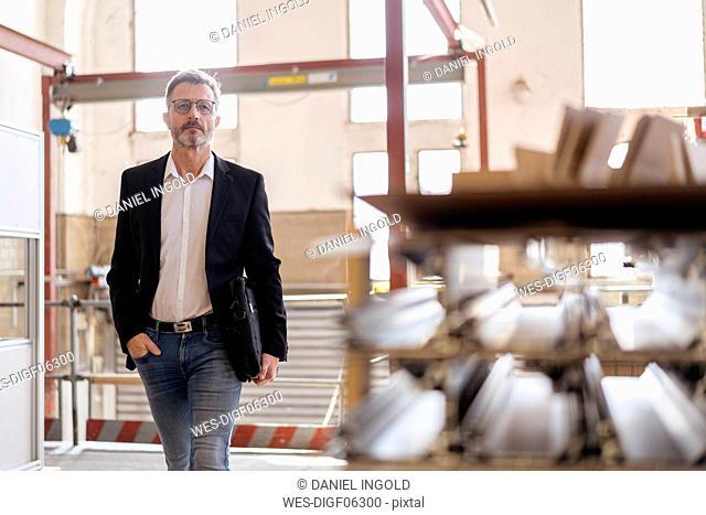Businessman walking in factory warehouse