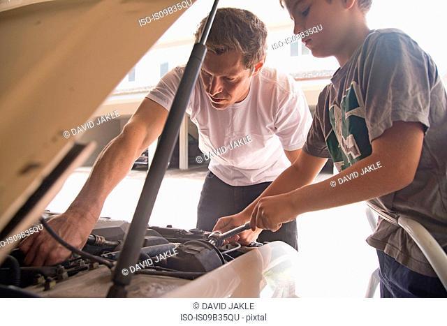 Father showing son car maintenance under car hood