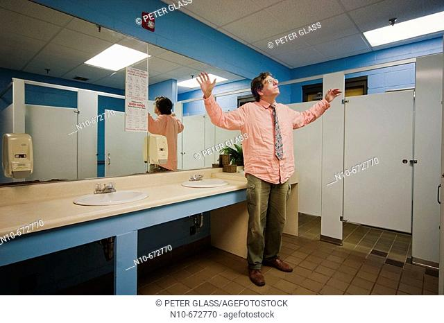 Man, wearing glasses and a tie, standing in an office building bathroom