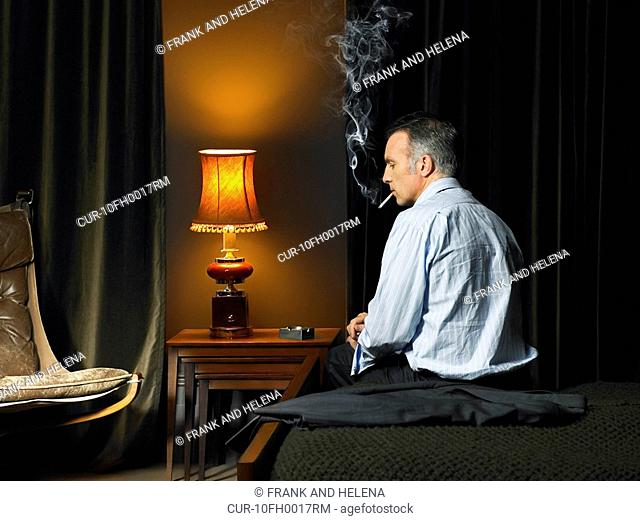 Man sitting on bed with back to camera, looking disappointed and smoking a cigarette