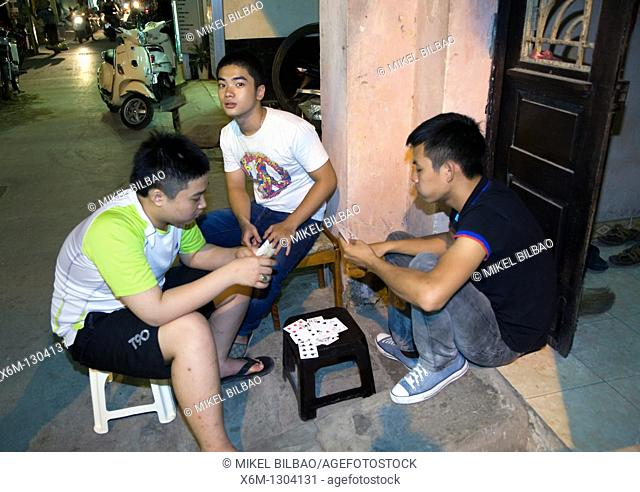 young men playing cards in the street  Hanoi, Vietnam