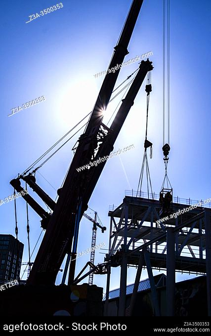 Two workmen hoisted up at a construction site at Strijp-S, Eindhoven, The Netherlands, Europe