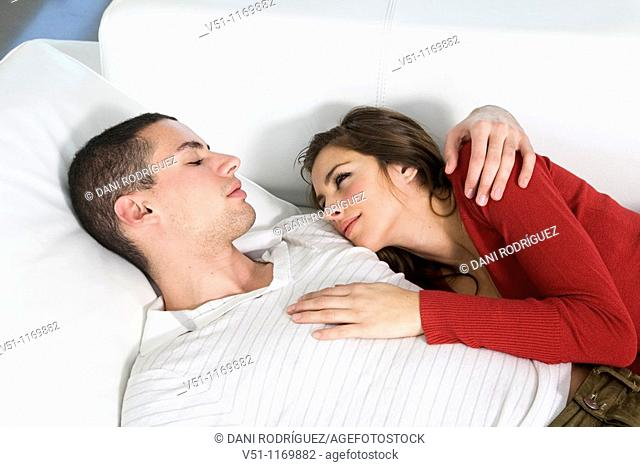 Portrait of a couple in sofa in love looking at each other
