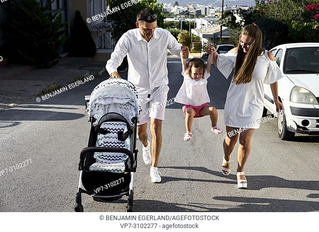 parents holding daughter up in hands, walking on street, vibrant, with buggy, parenthood, family, one child, candid, unposed