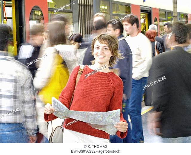 young woman standing in front of the sub way with a city map, people in the background, trying to get in
