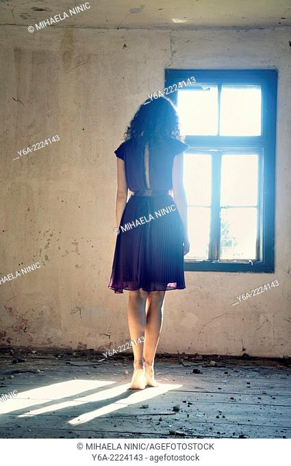 Young woman standing by the window