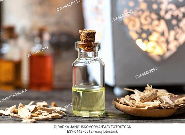 A bottle of essential oil with cedar wood chips