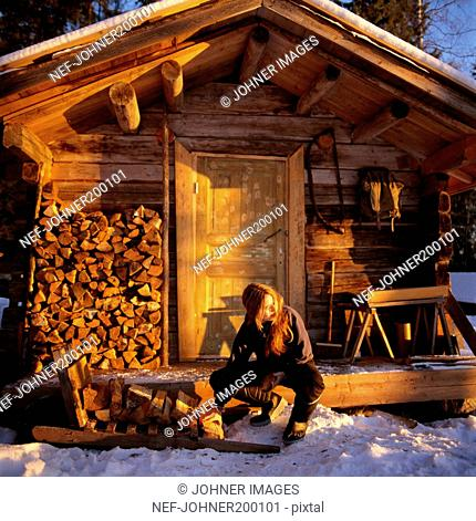 Woman crouching in front of cottage