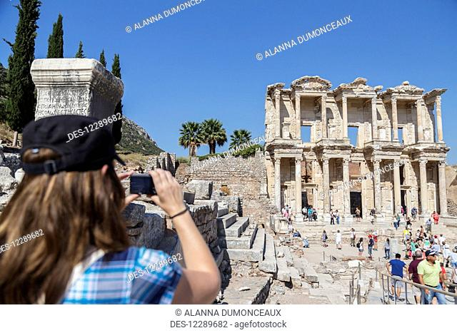 A female tourist takes a photo of the Library of Celsus in the ruins of Ephesus; Ephesus, Izmir, Turkey