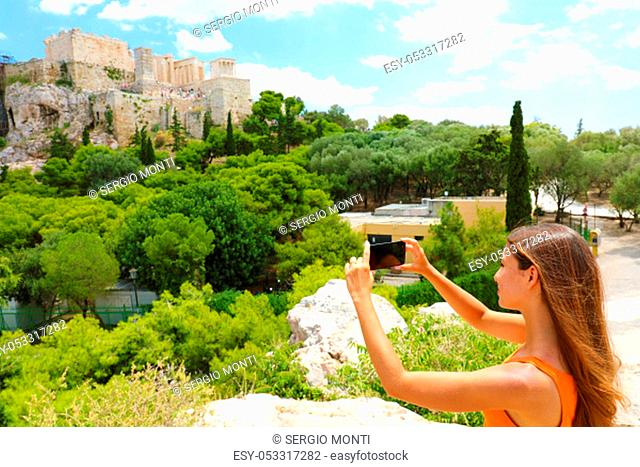 Cute young woman takes a picture of the Acropolis, Athens, Greece. Famous ancient Greek Acropolis is the main landmarks of Athens