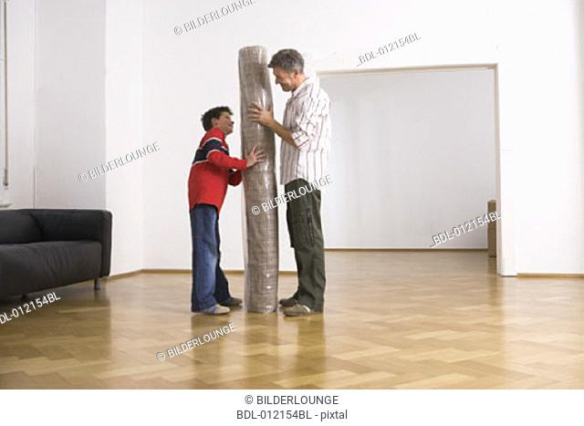 father and son having fun with carpet