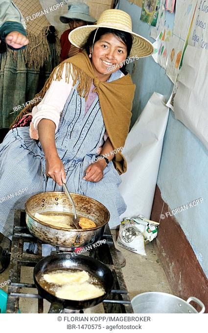 Woman in traditional dress of the Quechua preparing fried dumplings, Bolivian Altiplano highlands, Departamento Oruro, Bolivia, South America