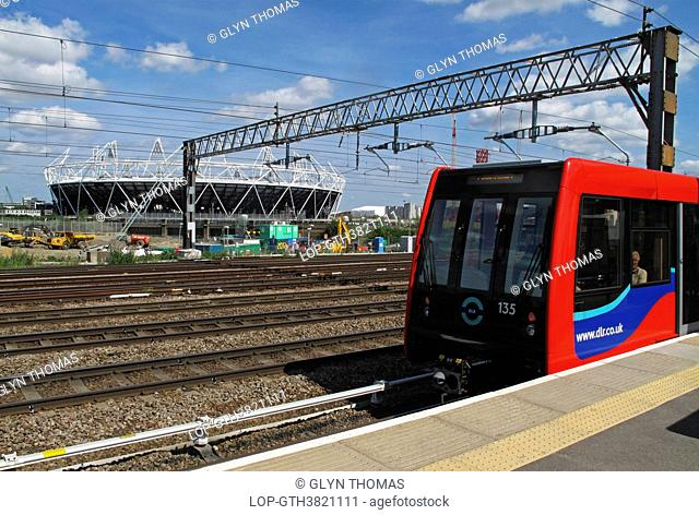 England, London, Stratford. A Docklands Light Railway train alongside a platform with the Olympic Stadium in the background