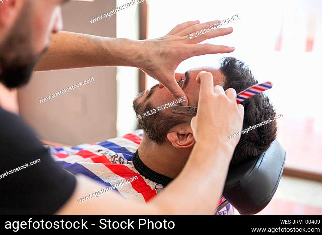 Male hairdresser trimming man's beard with razor at salon