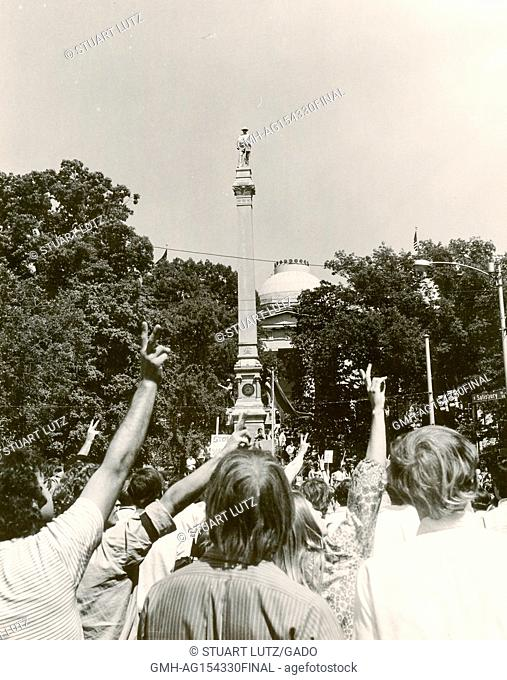 A group of students wearing hippie attire hold up their fingers in a peace sign gesture as they march on the capitol of North Carolina
