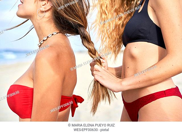 Young woman braidng the hair of her friend on the beach