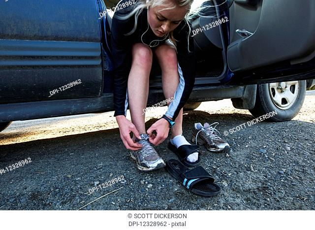 A Young Woman Sits On The Seat Of Her Car With The Door Open Changing Shoes Before Going For A Run; Homer, Alaska, United States Of America